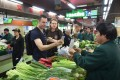 Tim Clancy (left) of Australia, a resident for six years in the Zhejiang provincial capital of Hangzhou, takes his American friend (centre) to a vegetable market where he pays for vegetables through mobile payment on April 14, 2017. Photo: Xinhua