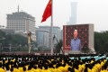 President Xi Jinping, seen on a giant screen, sings the national anthem during a flag-raising ceremony at the Tiananmen Square event on Thursday. Photo: Reuters