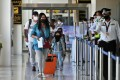 Passengers from Abu Dhabi arrive at Phuket airport on Thursday. Photo: AFP
