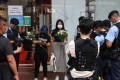 Police stop and search people in Causeway Bay, especially those holding flowers, a day after an officer was knifed in the area, with the attacker stabbing himself afterwards. Photo: K. Y. Cheng