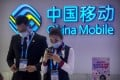 In this Oct. 14, 2020 file photo, staff members use their smartphones at a display from Chinese telecommunications firm China Mobile at the PT Expo in Beijing. Photo: AP