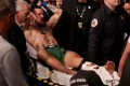 Conor McGregor is carried out of the arena on a stretcher after breaking his leg against Dustin Poirier at UFC 264. Photo: AFP