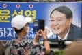 A supporter takes a photo of a banner with an image of Yoon Suk-yeol in Seoul. Photo: AP