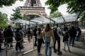 Visitors wait in line as they arrive to visit the Eiffel Tower in Paris on Friday. The French capital city attraction reopened to visitors on Friday, after nine months of shutdown caused by the Covid pandemic. Photo: AFP