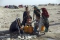 Internally displaced Afghans, who fled their home because of fighting between the Taliban and Afghan security personnel, fill water containers on the outskirts of Mazar-i-Sharif, northern Afghanistan, on July 8, 2021. Photo: AP Photo