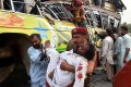 A security official carries a man injured in a bus accident near Dera Ghazi Khan in Pakistan on Monday. Photo: AFP