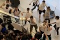 A video capture shows men in white armed with wooden sticks chasing and assaulting people at Yuen Long MTR station on July 21, 2019. Photo: Handout