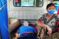 A relative sits with a coronavirus patient who is being taken to a hospital in the town of Kale, as Myanmar battles a deadly uptick in cases. Photo: Reuters