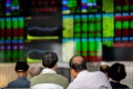 Investors monitor stock prices inside a brokerage house in Shanghai. Photo: AFP