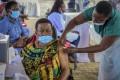 A woman receives a coronavirus vaccination at the Kololo airstrip in Kampala, Uganda. Photo: AP