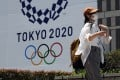 A passer-by walks past the logo of the Tokyo 2020 Summer Olympics in Tokyo. Photo: AP