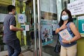 Hong Kong resident Evangeline Solis Santos has her photo taken by friends after being vaccinated with BioNTech earlier this month in Sai Ying Pun. Photo: May Tse
