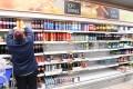 A supermarket worker stocks soft drinks in London. Photo: EPA-EFE
