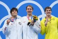 Silver medallist Jay Litherland, gold medallist Chase Kalisz (both from the US) and bronze medallist Brendon Smith from Australia pose maskless with their medals after the final of the men's 400m individual medley swimming event. Photo: AFP