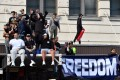 Protesters climb an awning outside Sydney Town Hall during an anti-lockdown rally over the weekend, which could become a superspreader event. Photo: Reuters