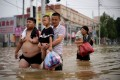 People carrying children and supplies wade through floodwater following record-breaking rainfall in China's Henan province. Photo: Reuters