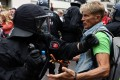 Police scuffle with a demonstrator in Berlin. Photo: Reuters