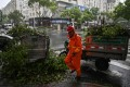 A worker clears fallen tree branches in Ningbo ahead of Typhoon In-fa's arrival. Photo: AFP