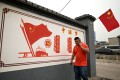 """A man walking past a propaganda mural that reads """"Chinese Dream: make the country prosperous and strong, rejuvenate the nation"""" along a street in Beijing. Photo: AFP"""