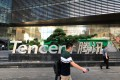 People walk past a Tencent sign at the company headquarters in Shenzhen. Photo: Reuters