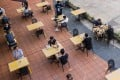 Customers sit at socially distanced tables outside a restaurant in Singapore. Photo: Bloomberg