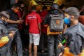Delivery riders for Zomato and Swiggy, two Indian start-ups, wait to collect orders outside a restaurant in Mumbai. Photo: Bloomberg