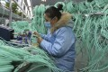 A worker assembles optic fibre cables at a factory in Suixi in central China's Anhui province. Photo: AP