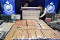 Police display money seized in a crackdown on triad-run syndicates suspected of attempting to defraud a government-backed loan scheme. Photo: Felix Wong