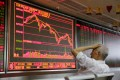 An investor looks at a board showing stock information at a brokerage in Beijing. Photo: Reuters