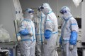 Laboratory technicians wearing personal protective equipment handle samples to be tested for Covid-19 in Wuhan, China, following an outbreak of the Delta variant in the city. Photo: AFP