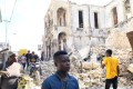 People walk along the street next to destroyed buildings following an earthquake in Jeremie, Haiti on Saturday. Photo: Courtesy of Twitter@JCOMHaiti/ via Reuters