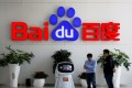 Men interact with a Baidu AI robot at its headquarters in Beijing. Photo: Reuters