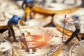 Concept photo of figurines of miners on a stack of bitcoin. Photo: Shutterstock