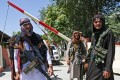 Taliban fighters stand guard along a road near Zanbaq Square in Kabul on Monday. Photo: TNS