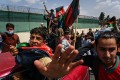 People carrying Afghanistan's national flag march in the streets of Kabul despite the presence of Taliban fighters around them. Photo: TNS