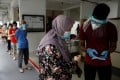Residents queue up for Covid-19 swab tests in Singapore. File photo: Reuters