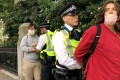 Police officers detain Extinction Rebellion climate demonstrators near the Science Museum in London on Monday. Photo: Extinction Rebellion UK via Reuters