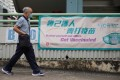 A man walks past a sign urging people to get vaccinated outside the Hiu Kwong Street Sports Centre in Kwun Tong. Photo: Winson Wong