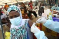 A woman receives a vaccination against Ebola in the slum of Alakro in Abidjan, Ivory Coast in August. Photo: Reuters
