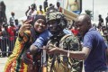 A woman takes a picture with Guinean special forces during celebrations at the Palace of the People in Conakry, Guinea. Phot: EPA