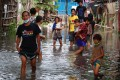 Villagers wade though floodwaters after the Philippines was hit by two major tropical storms in a week. Photo: EPA-EFE