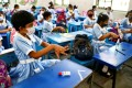 Pupils apply hand sanitiser while attending a class in Dhaka on Sunday as schools in Bangladesh reopened after nearly one and a half years of closure. Photo: Reuters