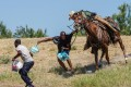 A US Border Patrol agent on horseback tries to stop a Haitian migrant from entering a Texas encampment on the banks of the Rio Grande. Photo: AFP