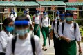 Students wearing masks and face shields leave after attending the first day of school in Yangon, Myanmar. Photo: AFP