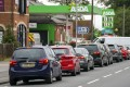 Cars queue outside a petrol station in England. Photo: AP