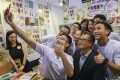 Financial Secretary Paul Chan (in black jacket) poses for a selfie with a group of admirers at the Hong Kong Book Fair. Photo: K. Y. Cheng