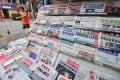 A man walks past a display of newspapers at a news-stand in Beijing on July 23, 2009. In a new draft document reiterates rules in place since 2005 banning private capital in news media, which the government has previously selectively enforced. Photo: AFP