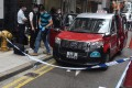 Police officers investigate the killing of a Hong Kong taxi driver on Tuesday. Photo: Handout
