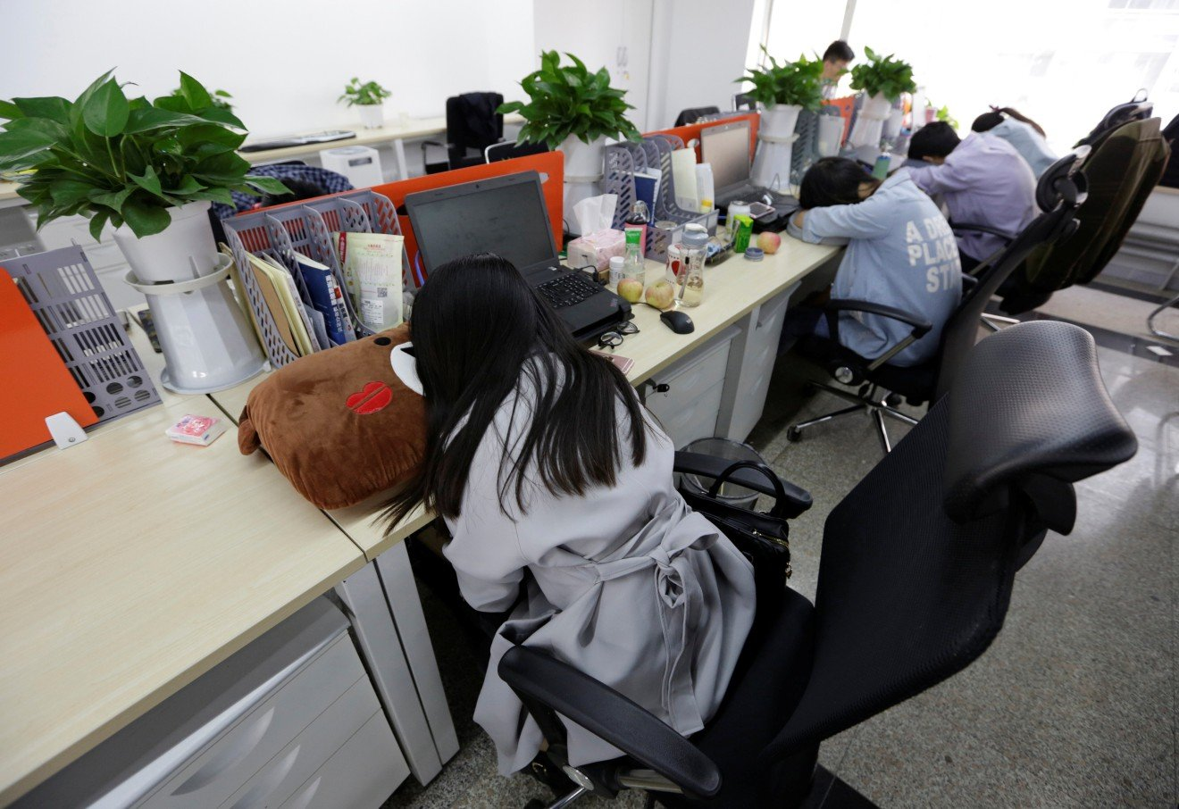 Employees of Goopal Group, a fintech company in Beijing, nap at their desks.
