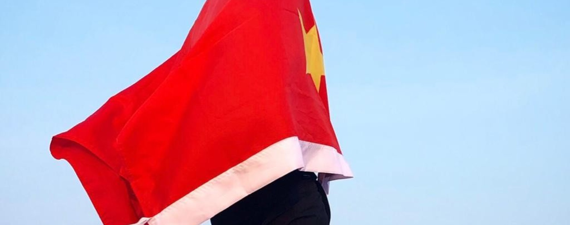 Ash Dykes wrapped in the Chinese flag while walking along the Yangtze River in China. Photo: Handout